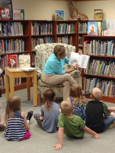 Ms. Sally reads to children.